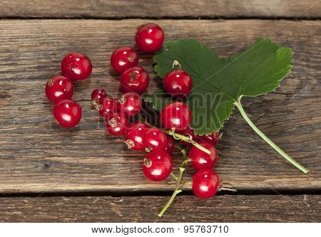 ripe redcurrant with leaf on rustic wooden background