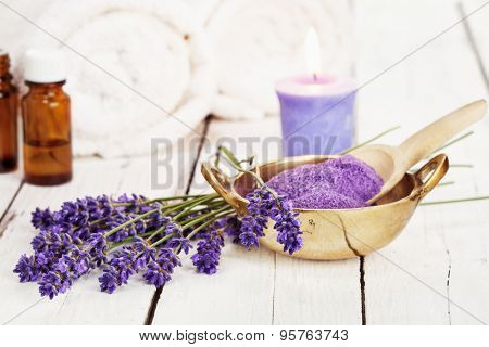 lavender flowers, bath salt, massage oil, scented candle and towels on rustic white background, high key image