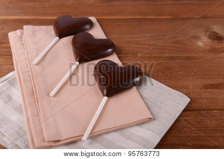 Chocolate heart shaped candies on sticks with napkin on wooden background