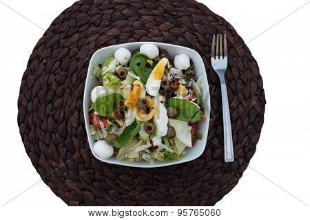 High Angle View of Gourmet Nutritional Salad Food with Eggs on Bowl, Placed on Top of Brown Placemat Against White Background.