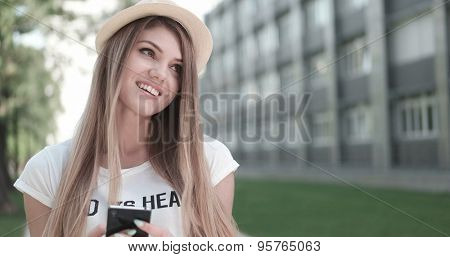 Close up Pretty Blond Woman Wearing Hat, Holding her Mobile Phone While Looking Into Distance Outside the Building.