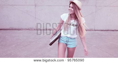 Attractive trendy young female student walking along with the books happy