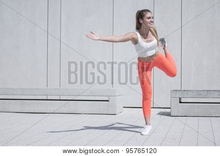Full Length Shot of a Happy Sporty Pretty Girl Doing an Outdoor Stretching Exercise While Looking Into Distance.
