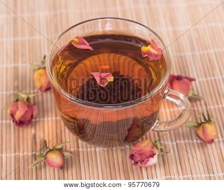 transparent cup of tea and withered rose petals