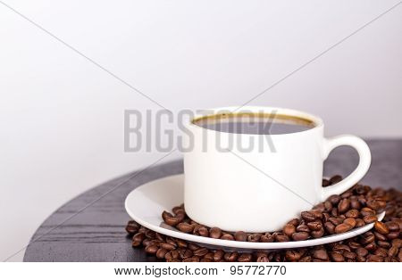 isolated white cup of coffee with coffee beans on dark table