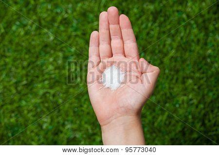 Human hand holding crystal sugar close up