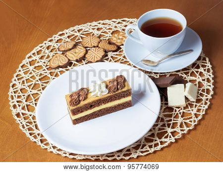 Sweet Cake With Cup Of Tea, Cookies  And Chocolate On Wooden Table