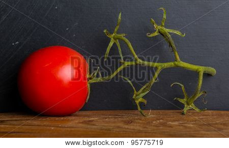 Red Tomato With Twig On A Table