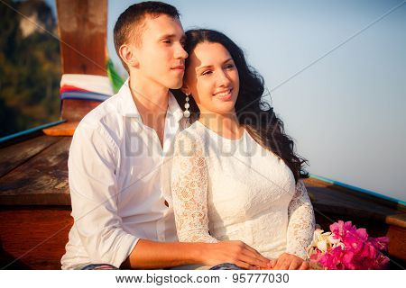 Bride And Groom Sit On Longtail Boat