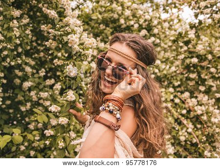 Hippie Young Woman Among Flowers Looking Through Sunglasses