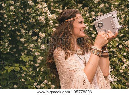 Bohemian Young Woman Among Flowers Using Retro Camera