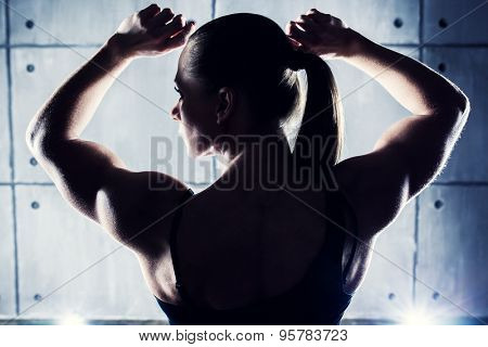 Strong woman bodybuilder back view. Contrast silhouette on wall background.