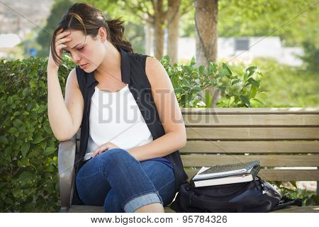 Depressed Young Woman Sitting on Bench Outside at a Park.