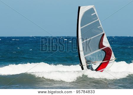 windsurfer moving on the waves of slight stormy sea