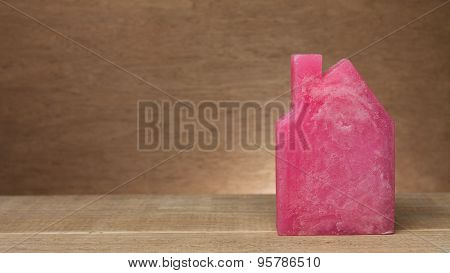 Figure of small house from wax on wooden background