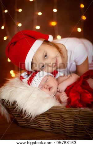 Christmas sleeping newborn baby with sister