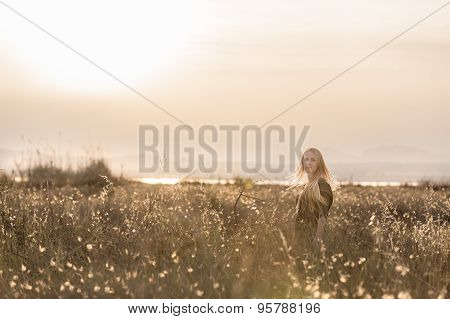 Young happy woman in field on sunset