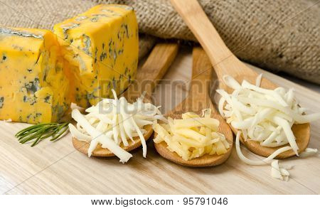 Grated Cheese In Wooden Spoons
