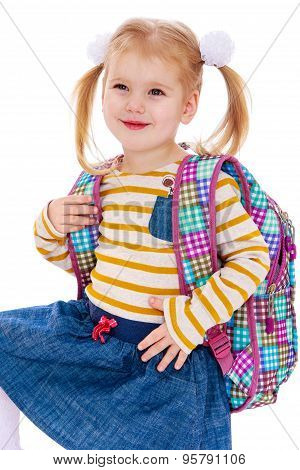 Smiling little blonde girl schoolgirl with long tails on the hea