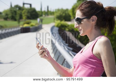 Pink Shirt Woman With Phone In Park