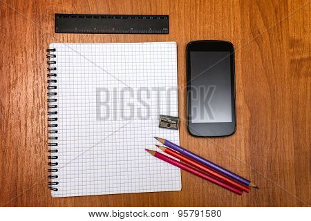 Pencils, Pencil Sharpener, Ruler And Mobile Phone Lying On Notebook. School.