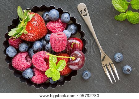 Mix Of Fresh Berries In A Small Round Metal Backing Mold And Fork On The Side, On Stone Gray Backgro