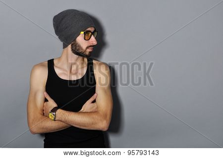 Handsome young bearded man in yellow sunglasses and hat looking away. On gray background.
