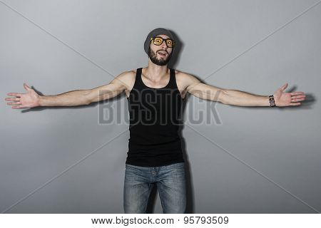 Handsome young bearded man in glasses. On gray background.