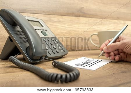 Closeup Of Male Receptionist Writing The Word Urgent