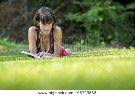 Young Woman Relaxing Reading On The Grass