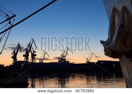 Cranes At The Docks In Sunset