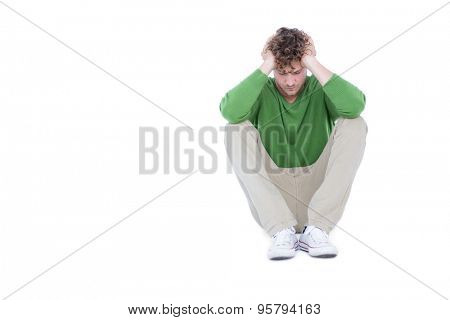 Sad casual man sitting with hand on head on white background