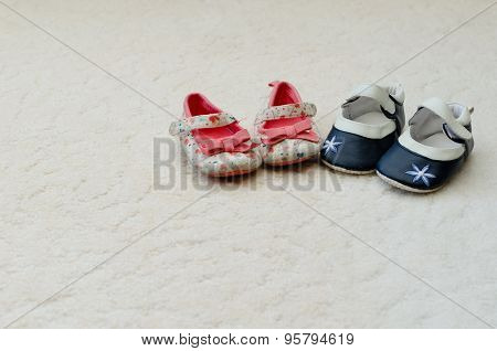 Two Pairs Of Baby Girl First Shoes One Blue With Flower On The Toe And One White With Floral Pattern
