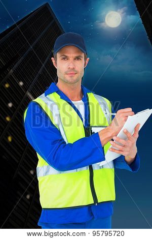 Confident supervisor writing notes on clipboard against city at night