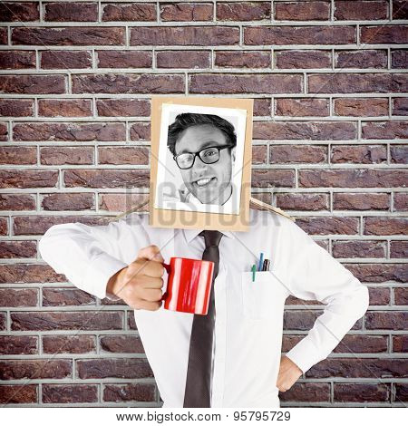 Businessman with photo box on head against red brick wall