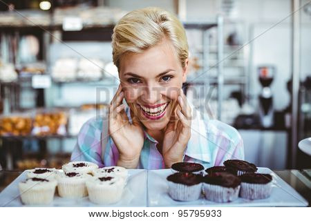 Pretty woman looking at cup cakes at the bakery