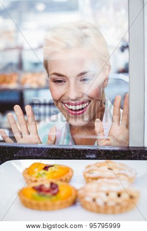 Puzzled pretty woman looking at a fruit pie at the bakery through the glass