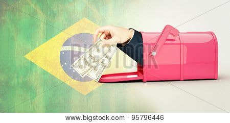 Hand holding hundred dollar bills against brazil flag in grunge effect