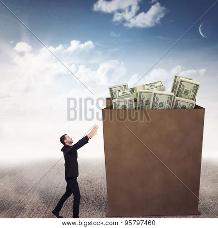 Businessman with arms raised catching something against blue sky