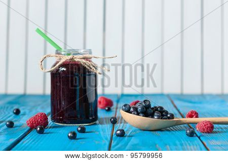 Mason jar with berry jam or marmalade and fresh raspberry on a rustic wooden table. Cooking backgrou