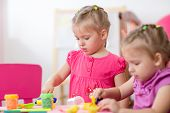 stock photo of day care center  - Little girls learning to work colorful dough in nursery at home or day care center  - JPG