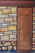 image of stone house  - Red entrance door in front of residential house and stone wall - JPG