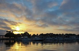 foto of glorious  - A Glorious Sunrise is Reflected in the Calm Waters of a Marina - JPG