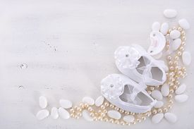 image of teething baby  - Baby shower neutral white background with baby booties pearls and sugar almonds on shabby chic rustic wood table with copy space - JPG