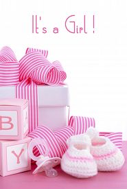 stock photo of teething baby  - Baby shower Its a Girl pink gift with baby booties dummy and gift box on pink shabby chic wood table - JPG