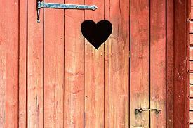 image of outhouse  - Outdoor toilet door with carved heart below iron hinge - JPG
