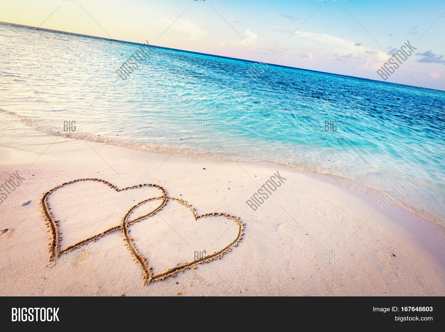 Two Hearts Drawn On Sand Of A Tropical Beach At Sunset Clear Turquoise Ocean