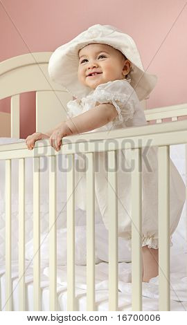 little child baby standing in bed smiling