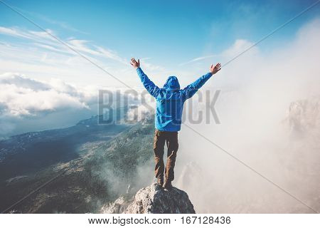 Man Traveler on mountain summit enjoying aerial view hands raised over clouds Travel Lifestyle success concept adventure active vacations outdoor happiness freedom emotions