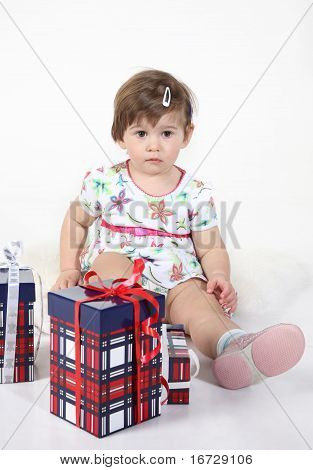little girl sits with three gift boxes